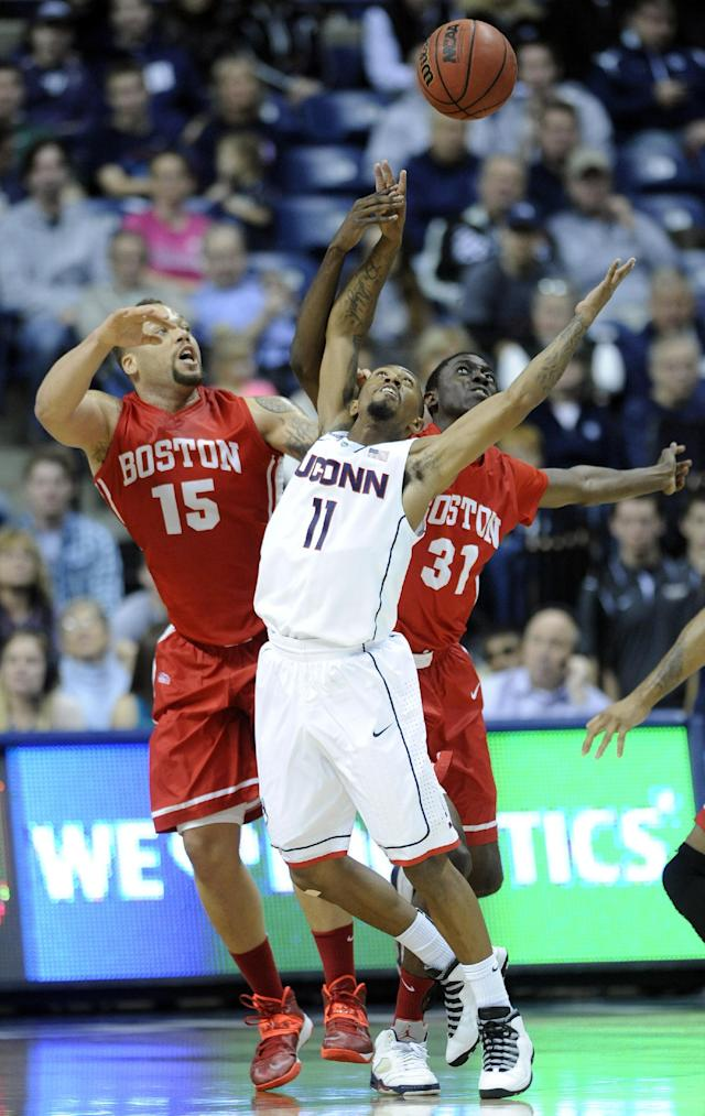 Boston University's Dom Morris (15) and Malik Thomas (31) fight for a rebound with Connecticut's Ryan Boatright (11) during the first half of an NCAA college basketball game in Storrs, Conn., on Sunday, Nov. 17, 2013. (AP Photo/Fred Beckham)