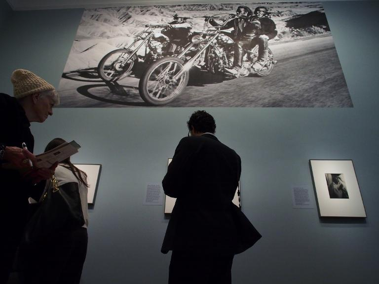 """A poster-sized still from the 1969 road movie """"Easy Rider"""" looms over museum-goers at a February 5, 2014 press preview of the """"American Cool"""" exhibition at the National Portrait Gallery in Washington, DC"""