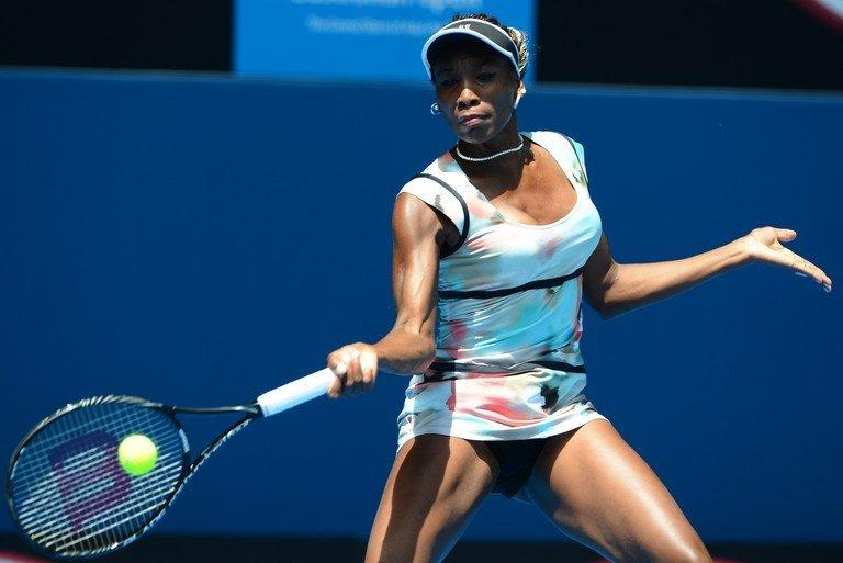 Venus Williams hits a return against Kazakhstan's Galina Voskoboeva during their first-round match at the Australian Open on January 14, 2013. Watched by sister Serena, Venus eased past Voskoboeva 6-1, 6-0