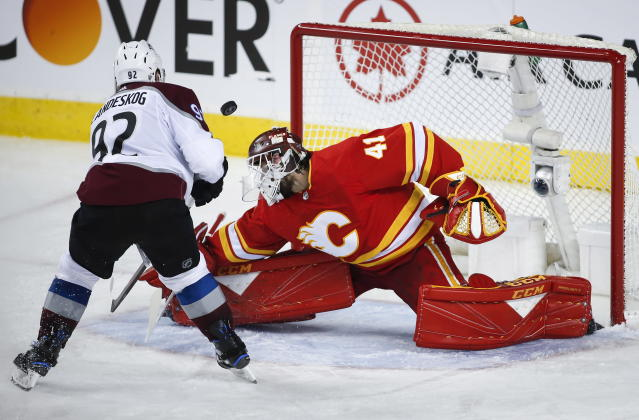 Calgary Flames goaltender Mike Smith (41) makes a save on Colorado Avalanche left wing Gabriel Landeskog (92) during the third period of an NHL hockey playoff game in Calgary, Alberta, Saturday, April 13, 2019. (Jeff McIntosh/The Canadian Press via AP)