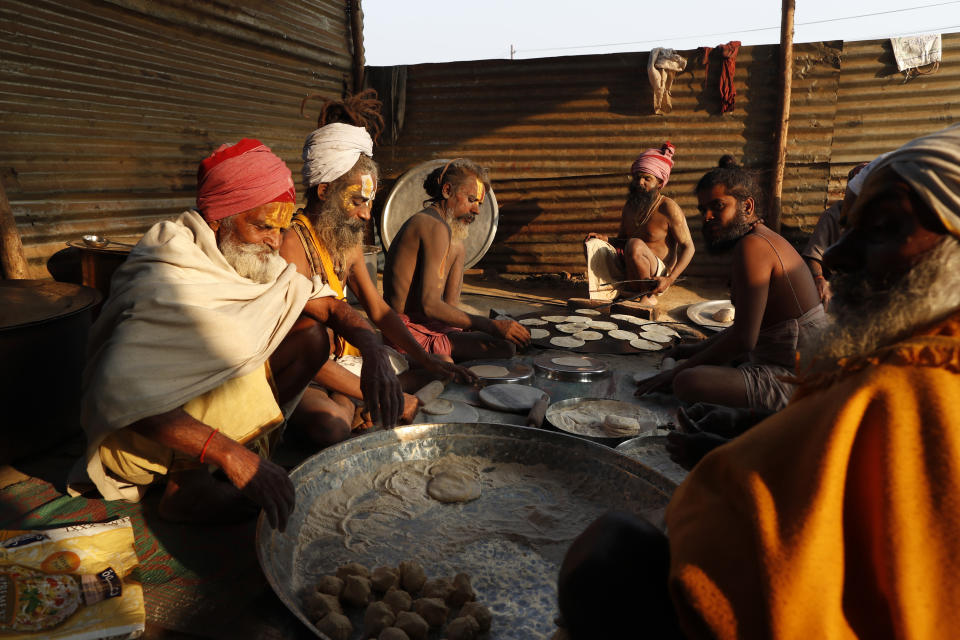 Hindu Holy men prepare food on the banks of the river Ganges during Magh Mela festival, in Prayagraj, India, Tuesday, Feb. 16, 2021. Millions of people have joined a 45-day long Hindu bathing festival in this northern Indian city, where devotees take a holy dip at Sangam, the sacred confluence of the rivers Ganga, Yamuna and the mythical Saraswati. Here, they bathe on certain days considered to be auspicious in the belief that they be cleansed of all sins. (AP Photo/Rajesh Kumar Singh)