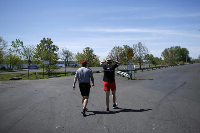 Fighter Kyle Daukaus, right, walks with his brother and training partner, Chris Daukaus, to exercise at Pleasant Hill Park, Saturday, May 2, 2020, in Philadelphia. Kyle, a rising star in the regional MMA promotion Cage Fury Fighting Championships, is still chasing his dream of getting the call to fight for UFC despite the coronavirus pandemic. (AP Photo/Matt Slocum)