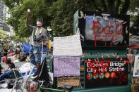 Protesters gather beside a subway station entrance at an encampment outside City Hall, Tuesday, June 30, 2020, in New York. New York City lawmakers are holding a high-stakes debate on the city budget as activists demand a $1 billion shift from policing to social services and the city grapples with multibillion-dollar losses because of the coronavirus pandemic. (AP Photo/John Minchillo)