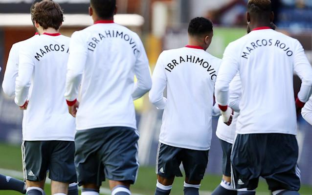<span>Manchester United's players warm up in shirts offering support for Marcos Rojo and Zlatan Ibrahimovic. Both players face long lay-offs after injuring their cruciate knee ligaments against Anderlecht</span> <span>Credit: REX </span>