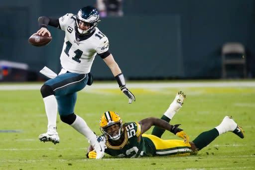 Green Bay Packers' Rashan Gary tries to stop Philadelphia Eagles' Carson Wentz during the first half of an NFL football game Sunday, Dec. 6, 2020, in Green Bay, Wis. (AP Photo/Matt Ludtke)