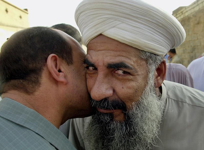 FILE - In this file photo taken Monday, Oct. 18, 2004, Sunni cleric Sheik Khalid al-Jumeili, right, is welcomed by a friend in Fallujah, Iraq, 40 miles (65 kilometers) west of Baghdad, Iraq. Police said gunmen shot dead Sunni cleric Khalid al-Jumeili, an organizer of the western city's Sunni protest camp, in a drive-by shooting. (AP Photo/Bilal Hussein, File)
