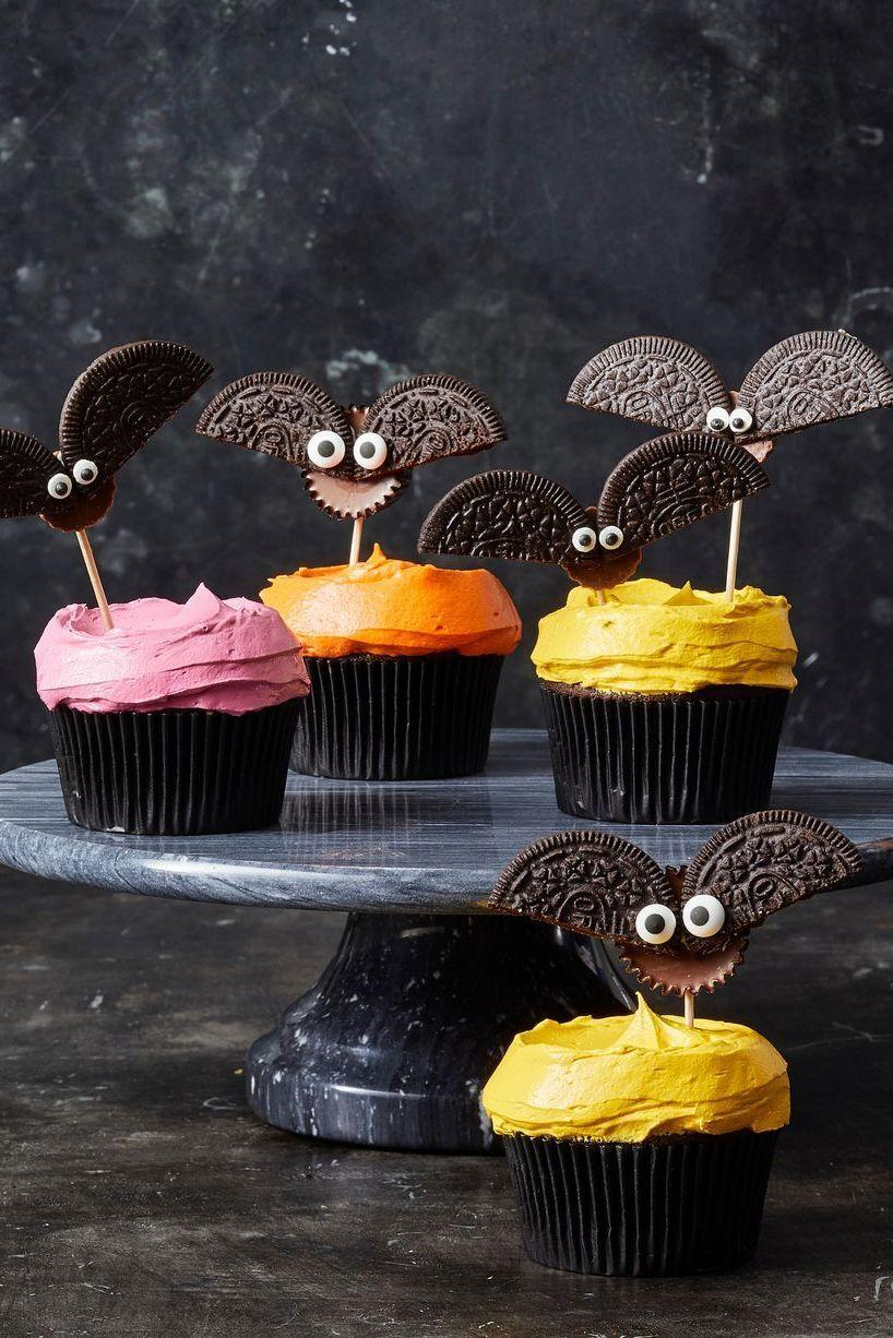 """<p>Deck out vibrant cupcakes with completely edible spooky bat decorations. </p><p><em><a href=""""https://www.goodhousekeeping.com/food-recipes/party-ideas/a28593120/cookie-bat-cupcakes-recipe/"""" rel=""""nofollow noopener"""" target=""""_blank"""" data-ylk=""""slk:Get the recipe for Cookie Bat Cupcakes »"""" class=""""link rapid-noclick-resp"""">Get the recipe for Cookie Bat Cupcakes »</a></em> </p>"""