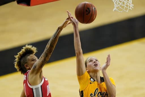 Iowa forward Logan Cook drives to the basket past Ohio State guard Rikki Harris, left, during the second half of an NCAA college basketball game, Wednesday, Jan. 13, 2021, in Iowa City, Iowa. Ohio State won 84-82 in overtime. (AP Photo/Charlie Neibergall)