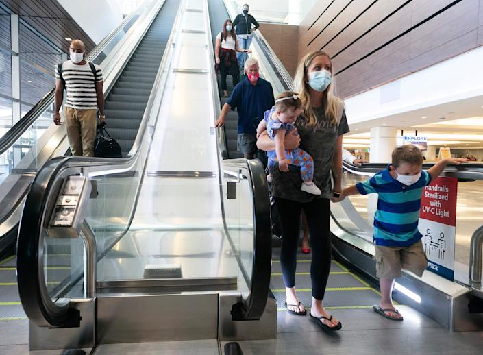 Brittney Evans of Goshen, Ind., carries her daughter, Mary Evans and holds hands with her nephew, Ayden Hussey, as they travel down an escalator with UV-C light technology to sterilize handrails, at Terminal 3 of Phoenix Sky Harbor International Airport on Sept. 3, 2020.