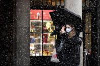 A woman wearing a face mask takes a photo on her phone in Covent Garden, London, Thursday, Dec. 3, 2020. Britain became the first country in the world to authorize a rigorously tested COVID-19 vaccine Wednesday and could be dispensing shots within days — a historic step toward eventually ending the outbreak that has killed more than 1.4 million people around the globe. (AP Photo/Alberto Pezzali)