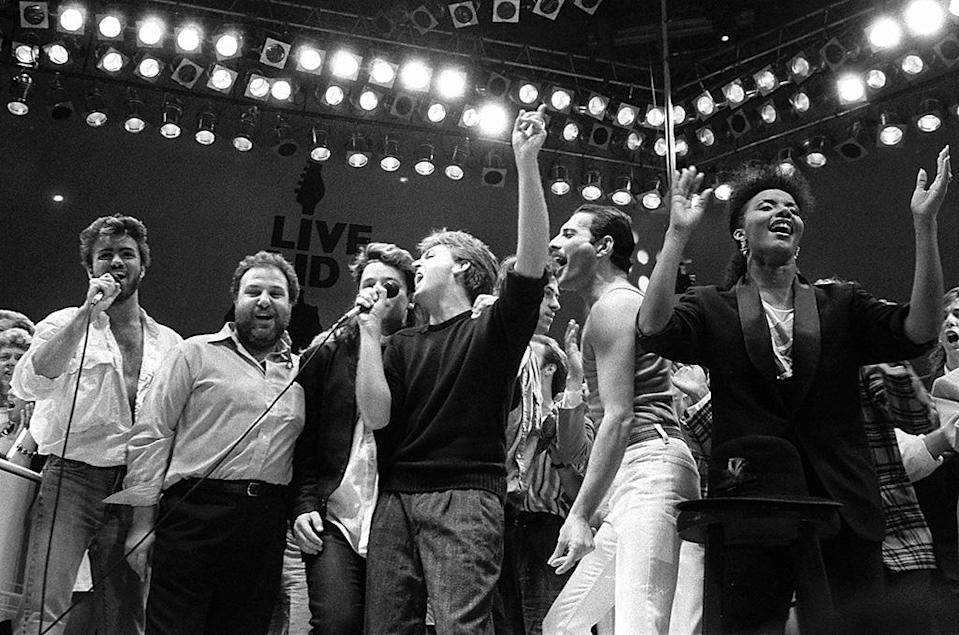 <p>A July 13, 1985, photo shows, from left, George Michael of Wham!, concert promoter Harvey Goldsmith, Bono of U2, Paul McCartney, concert organizer Bob Geldof, and Freddie Mercury of Queen in the finale of the <i>Live Aid</i> famine relief concert at Wembley Stadium in London. (Photo: AP/Joe Schaber) </p>