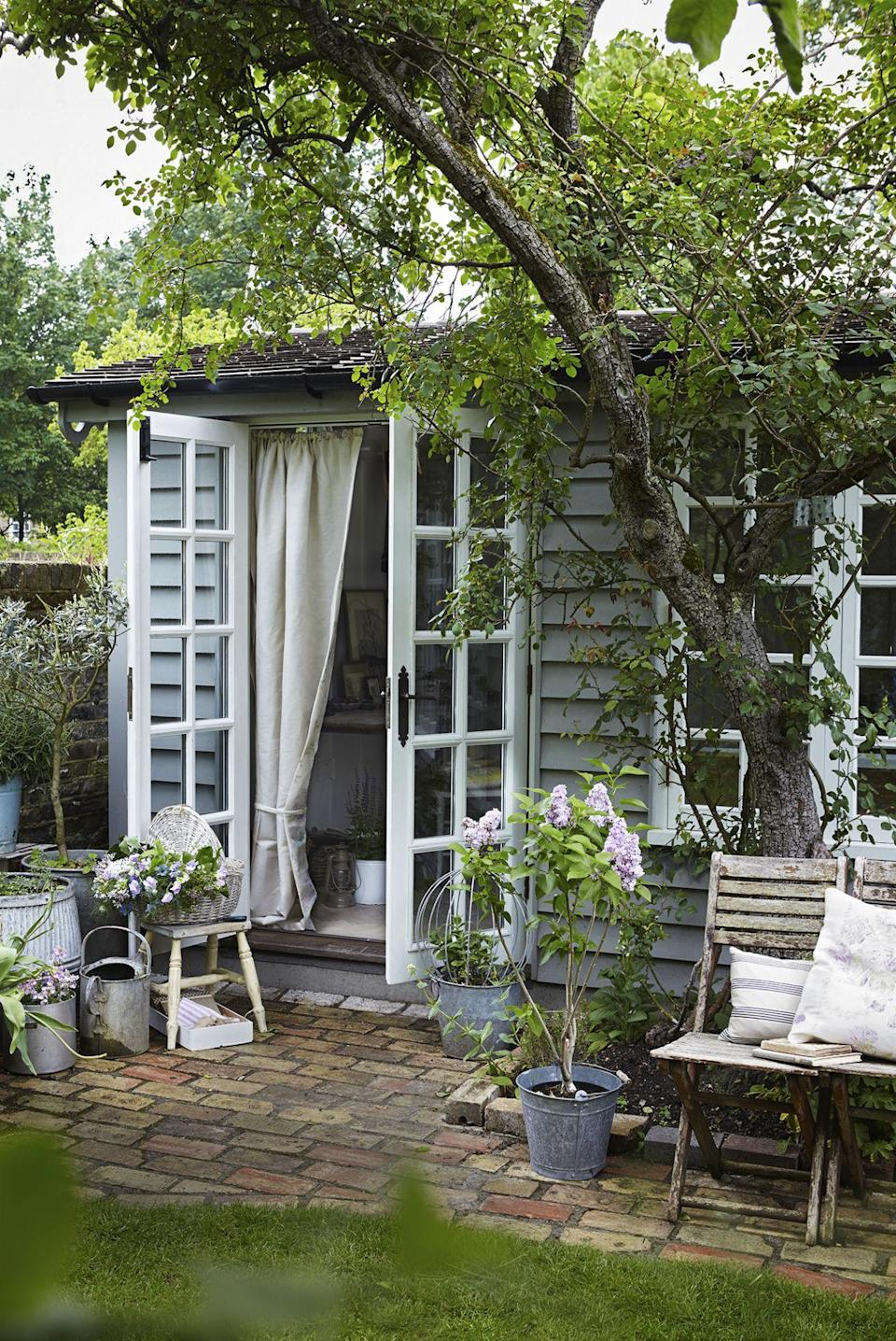 <p>Traditional wooden cladding in a subtle blue-grey brings rustic charm to this pretty garden studio, which serves as an extra room. </p>