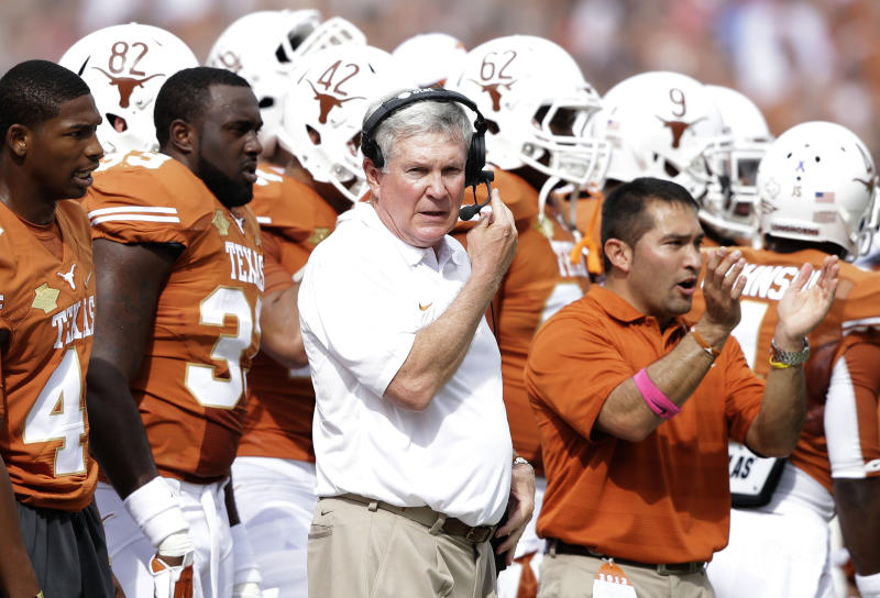 Texas head coach Mack Brown, center, talks into his headset during the first half of an NCAA college football game against Oklahoma at the Cotton Bowl Saturday, Oct. 12, 2013, in Dallas. (AP Photo/LM Otero)