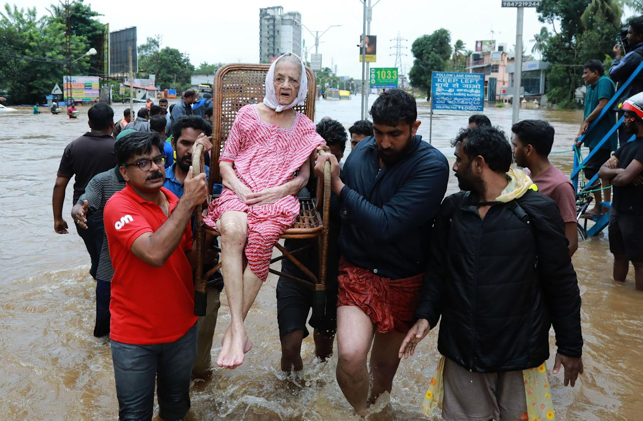 <p>Indian volunteers and rescue personal evacuate local residents in a residential area in Ernakulam district, in the Indian state of Kerala, on August 17, 2018. Troop reinforcements stepped up desperate rescue attempts in India's flood-stricken Kerala state on August 17 after more than 100 bodies were found in a day and a half, taking the crisis death toll to at least 164. (Photo by AFP/Getty Images) </p>