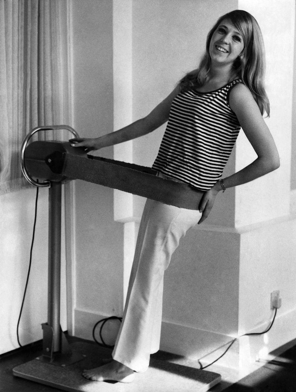 "<p>Not every aspect of the fitness world was evolving. The vibrating machines of the early 1900s came back as a trend in the 1960s. This woman uses a <a href=""https://wellness360magazine.com/fitness-trends/"" rel=""nofollow noopener"" target=""_blank"" data-ylk=""slk:vibrating belt"" class=""link rapid-noclick-resp"">vibrating belt</a>, which was believed to vibrate away the pounds.<br></p>"
