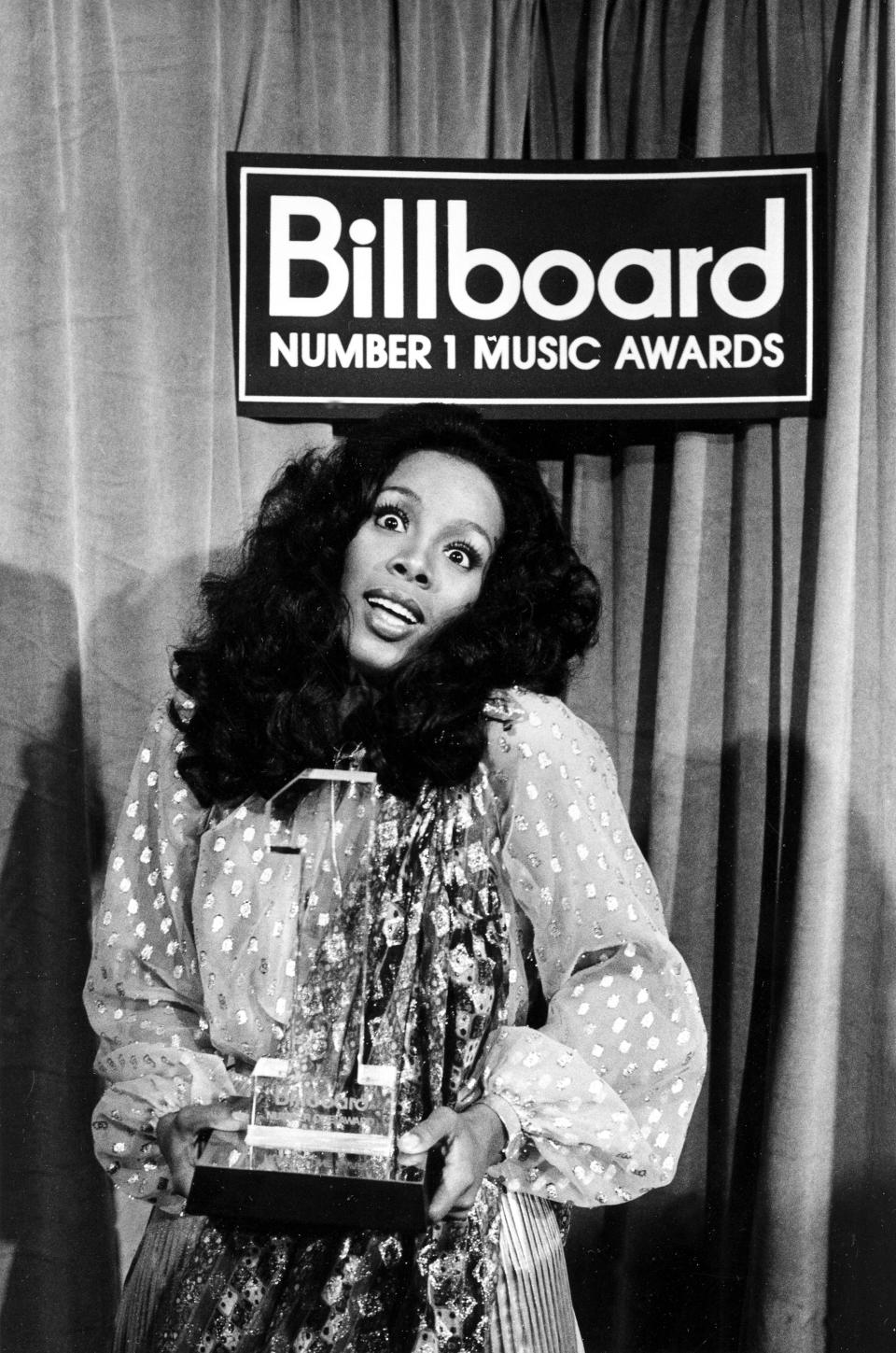 """FILE - In this Dec. 11, 1977 file photo,Donna Summer holds her award at the Billboard Number 1 Music Awards in Santa Monica, Calif. Summer, the Queen of Disco who ruled the dance floors with anthems like """"Last Dance,"""" """"Love to Love You Baby"""" and """"Bad Girl,"""" has died. Her family released a statement, saying Summer died Thursday, May 17, 2012. She was 63. (AP Photo/File)"""