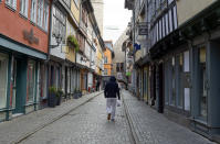 A man walks with his bag along an empty street at the 'Kraemerbruecke' (Kraemer Bridge), a most frequented tourist spot, in Erfurt, central Germany, Saturday, March 21, 2020. Erfurt's Kraemer Bridge is the longest inhabited bridge north of the Alps and features 32 buildings. For most people, the new coronavirus causes only mild or moderate symptoms, such as fever and cough. For some, especially older adults and people with existing health problems, it can cause more severe illness, including pneumonia. (AP Photo/Jens Meyer)