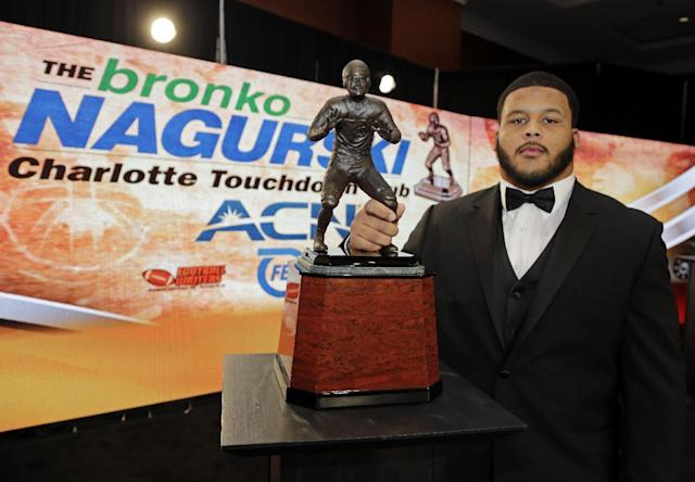 Pittsburgh's Aaron Donald poses for a photo with the Bronko Nagurski award for the NCAA college football defensive player of the year during a news conference in Charlotte, N.C., Monday, Dec. 9, 2013. Donald averaged 2.2 tackles for loss per game while ranking 10th in forced fumbles and 13th in sacks per game. (AP Photo/Chuck Burton)