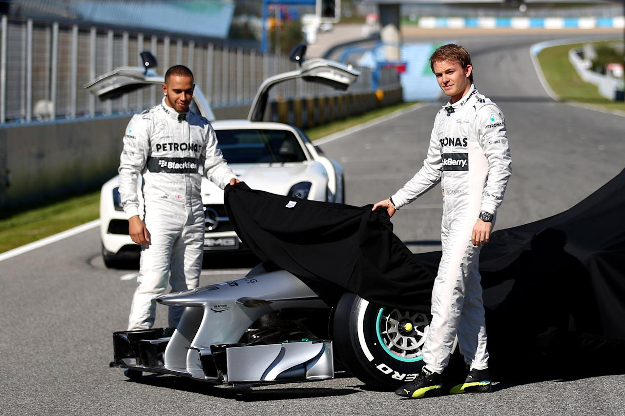 JEREZ DE LA FRONTERA, SPAIN - FEBRUARY 04:  Lewis Hamilton of Great Britain and Mercedes and Nico Rosberg of Germany and Mercedes unveil the new W04 car during the Mercedes GP F1 W04 Launch at Circuito de Jerez on February 4, 2013 in Jerez de la Frontera, Spain.  (Photo by Paul Gilham/Getty Images)