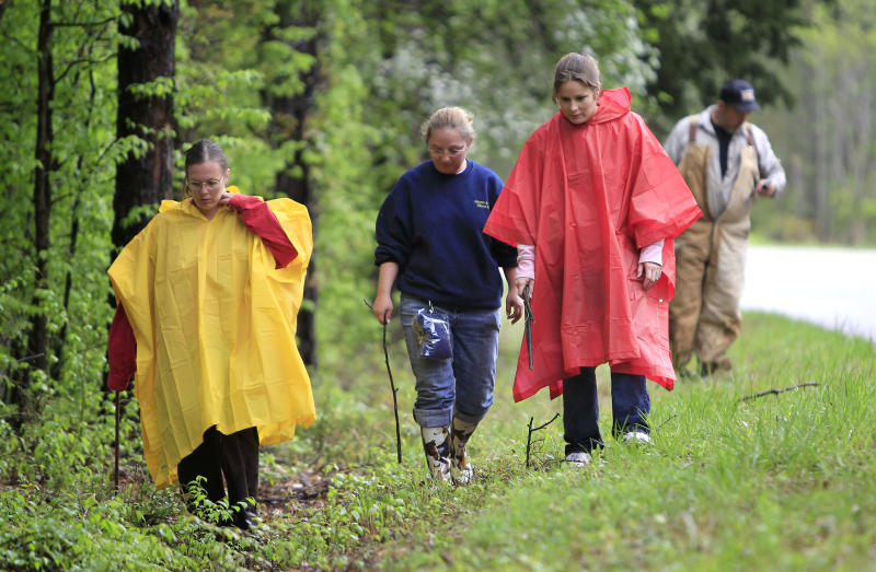 Paula Moore, left, Dana Kennedy, center, Christina Stout search along a rural road  for evidence in the disappearance of Holly Bobo on Friday, April 15, 2011, in Parsons, Tenn. Heavy rain Friday slowed the search through rugged terrain in western Tennessee for the woman officials say was abducted from her home by a man wearing camouflage. A midday break in the rain allowed dozens of law enforcement officers and volunteers to resume looking for the 20-year-old Bobo near Parsons, about 100 miles northeast of Memphis. (AP Photo/Mark Humphrey)