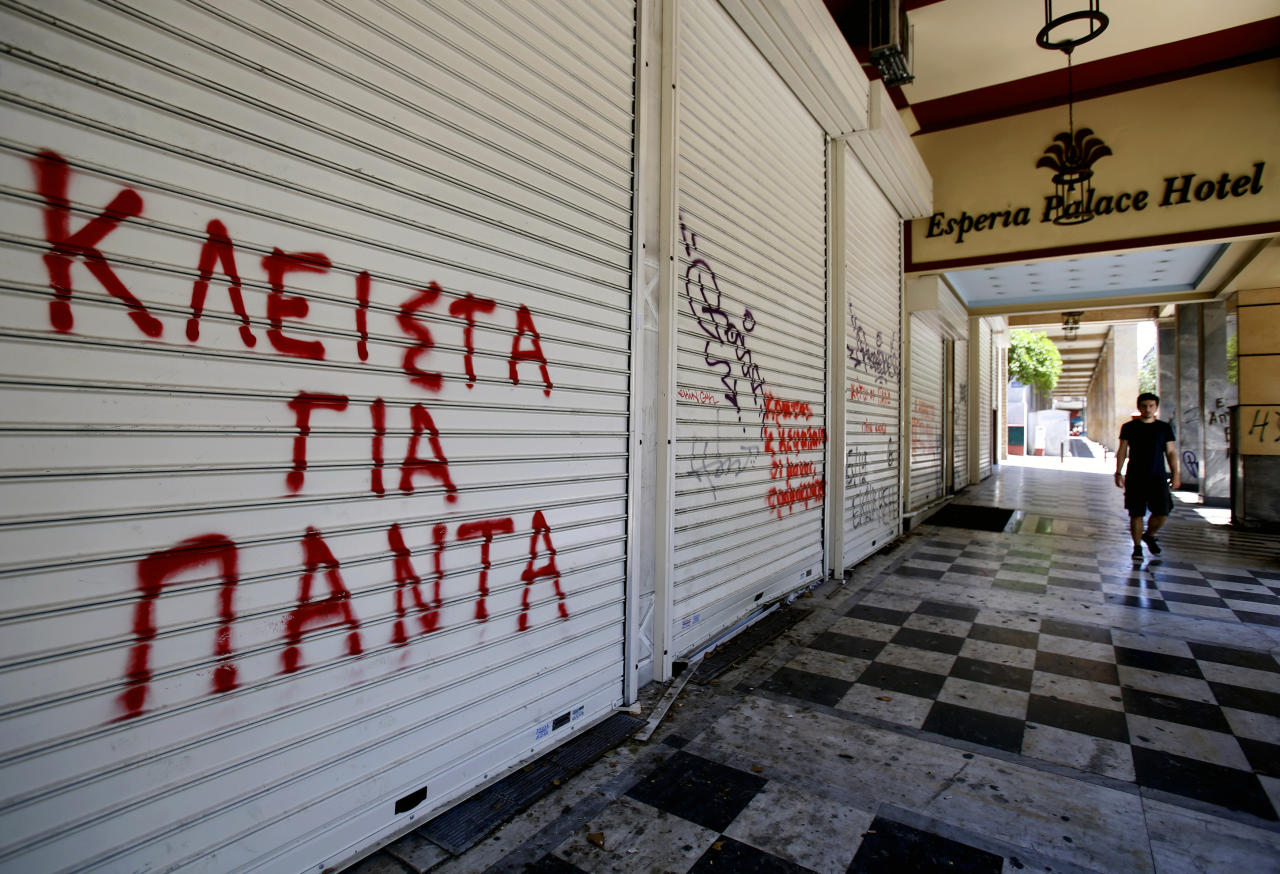 A tourist walks by the closed Esperia Palace Hotel in Athens Yannis Behrakis / Reuters