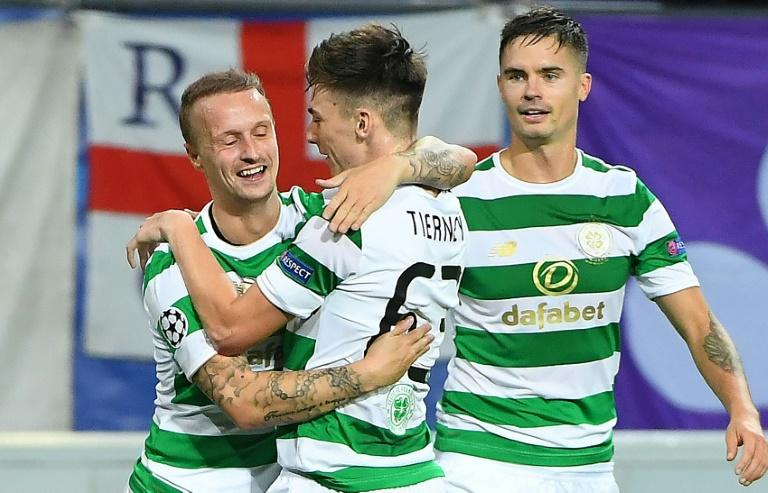 Leigh Griffiths of Celtic (L) celebrates with teammates Kieran Tierney (C) and Mikael Lustig after scoring a goal during an UEFA Champions League match in Brussels, on September 27, 2017