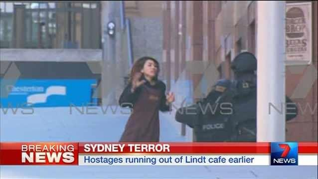 A distressed hostage runs out of the Martin Place Lindt cafe taken control by an alleged gunman. Photo:7News
