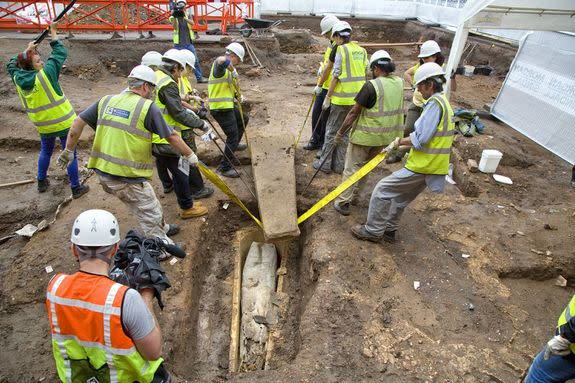 A team lifts the heavy lid of the stone coffin in Leicester.
