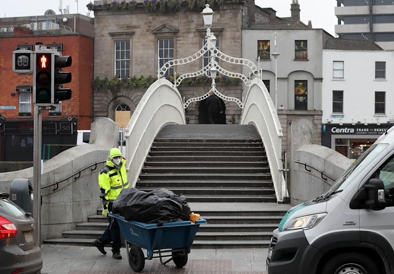 A council worker at the iconic Ha'Penny Bridge in Dublin's city centre as Ireland has introduced a number of sweeping measures in an effort to help curb the spread of the coronavirus.