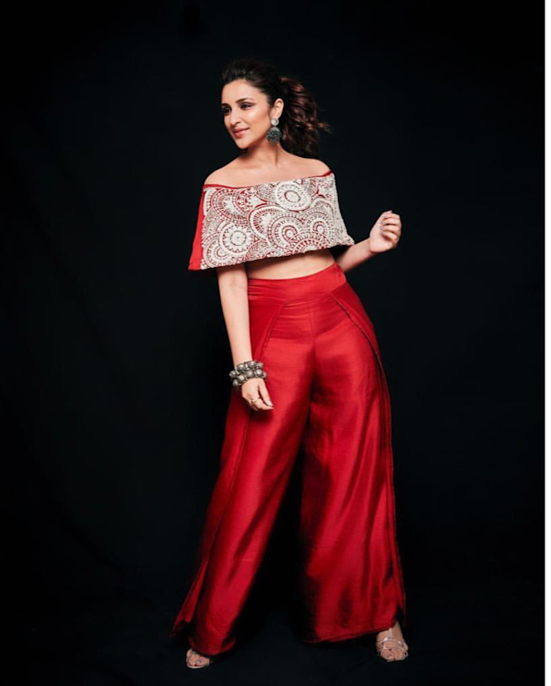 <p>These high-waist wide red pants with a matching red crop top was Parineeti's pick for the Umang show. One thing that we love about this attire is the intricate thread work on the top, and that is the only thing that commands praises in the otherwise confusing look. The oxidized earring with green stones, the heavy antique <em>kadahs </em>and a pair of silver strappy heels lack coordination with each other. </p>