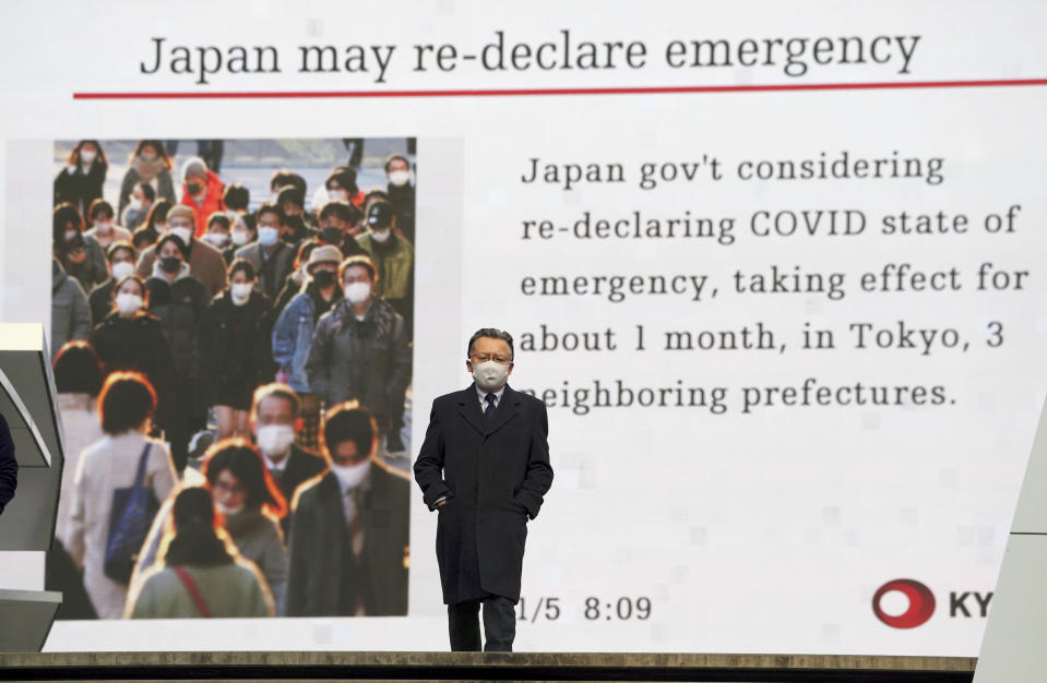 FILE - In this Jan. 5, 2021, file photo, a man wearing a mask against the spread of the coronavirus walks in front of a screen showing the news on possible Japan's State of Emergency in Tokyo. Opposition to the Tokyo Olympics is growing with calls for a cancellation as virus cases rise in Japan. The International Olympic Committee and local organizers have already said another postponement is impossible, leaving cancellation, or going ahead, as the only options. (AP Photo/Eugene Hoshiko, File)