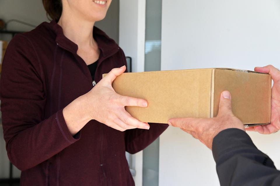 Woman receives package at her front door. Source: Getty Images