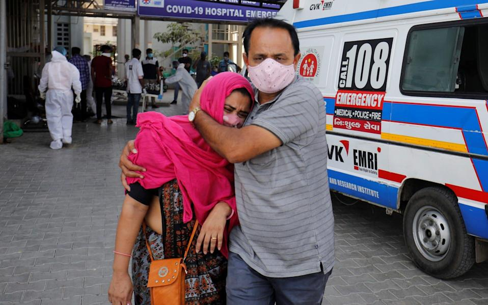 A woman is consoled after her relative died due to the coronavirus disease in Ahmedabad, India - Reuters