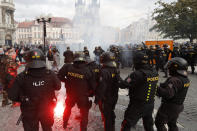 Police confront demonstrators as they protest against the COVID-19 restrictive measures at Old Town Square in Prague, Czech Republic, Sunday, Oct. 18, 2020. The Czech Republic has imposed a new series of restrictive measures in response to a record surge in coronavirus infections. Among the measures all sports indoor activities are banned and only up to 20 people are allowed to participate in outdoor sport activities also all bars, restaurants and clubs are closed while drinking of alcohol is banned at public places. (AP Photo/Petr David Josek)