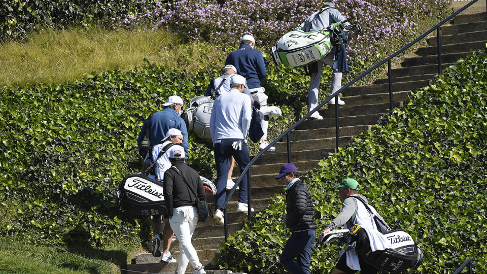 Golfers, caddies and staff, pictured here returning to the clubhouse after play was suspended.