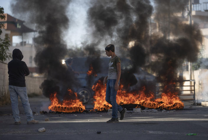 Palestinians burn tires and clash with Israeli army troops while securing the parameter of Palestinian American Muntasser Shalaby's house following a controlled explosion demolishing of the house, in the West Bank village of Turmus Ayya, north of Ramallah, Thursday, July. 8, 2021. Israeli forces on Thursday demolished the family home of Shalaby who is accused of being involved in a deadly attack on Israelis in the West Bank in May. (AP Photo/Nasser Nasser)