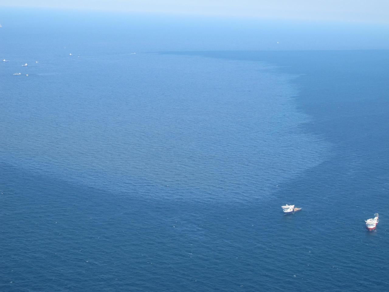 FILE - Two ships float near in a massive oil slick spreading in the Gulf of Mexico after the Deepwater Horizon drilling rig exploded off the coast of Louisiana. Florida Gov. Charlie Crist flew above the plume on in this April 27, 2010 file photo. BP agreed late Friday March 2, 2012 to settle lawsuits brought by more than 100,000 fishermen who lost work, cleanup workers who got sick and others who claimed harm from the oil giant's 2010 Gulf of Mexico disaster, the worst offshore oil spill in the nation's history. The momentous settlement will have no cap to compensate the plaintiffs, though BP PLC estimated it would have to pay out about $7.8 billion, making it one of the largest class-action settlements ever. After the Exxon Valdez disaster in 1989, the company ultimately settled with the U.S. government for $1 billion, which would be about $1.8 billion today. (AP Photo/Brendan Farrington, File)