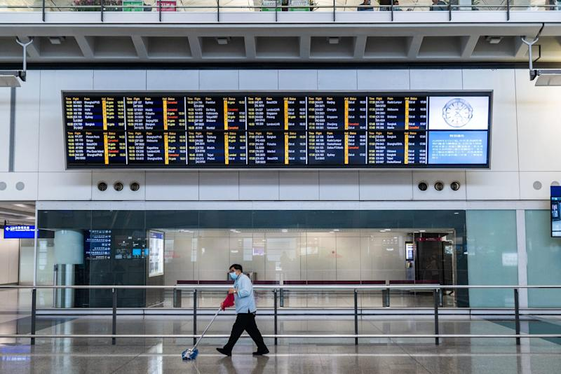 A cleaner mops the floor wearing a surgical mask in front of the flight information display at the arrival hall of Hong Kong international airpor 2