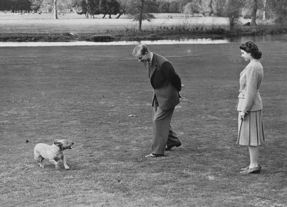 Prince Philip and Princess Elizabeth play with Susan, Elizabeth's corgi.