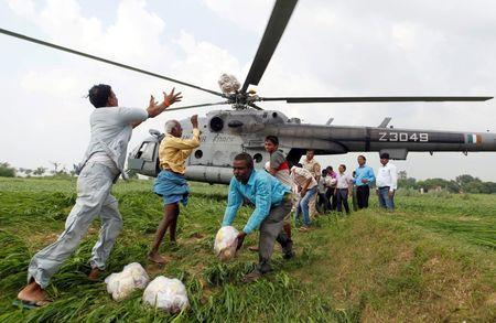 Food parcels are unloaded from an Indian Air Force helicopter to be distributed among those affected by flooding on the outskirts of Allahabad, India, August 25, 2016. REUTERS/Jitendra Prakash