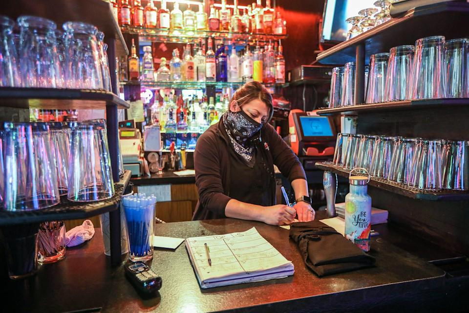 Tyla Sweeney, 41, of Howell works at Champs Pub in Brighton, Mich. as a bartender and takes phone orders during lunch on Jan. 5, 2021. Champs has been selected to receive a financial lifeline from the Barstool fund founded by Dave Portnoy to aid small businesses struggling to stay afloat during the coronavirus pandemic.