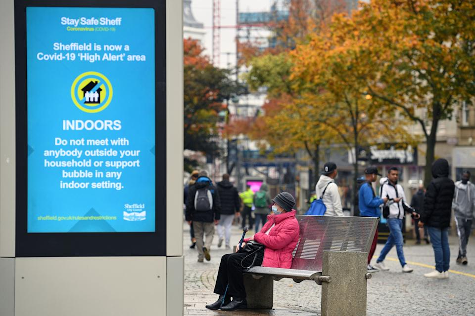 """A woman wearing a face mask or covering due to the COVID-19 pandemic, sits on a bench close to a display showing health advice in the shopping district in central Sheffield, south Yorkshire on October 21, 2020, prior to further lockdown measures as the number of novel coronavirus COVID-19 cases rises. - More than a million people in northern England will be banned from mixing with other households under tougher new coronavirus rules announced by government minister Robert Jenrick on Wednesday.  The county of South Yorkshire, which includes the city of Sheffield, will enter into """"very high alert"""" restrictions from 12.01am on Saturday (2301 Friday GMT). (Photo by Oli SCARFF / AFP) (Photo by OLI SCARFF/AFP via Getty Images)"""