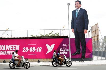 FILE PHOTO: People ride motorcycles past an image of Maldives President Abdulla Yameen on a road ahead of the presidential election in Male, Maldives September 19, 2018. REUTERS/Ashwa Faheem