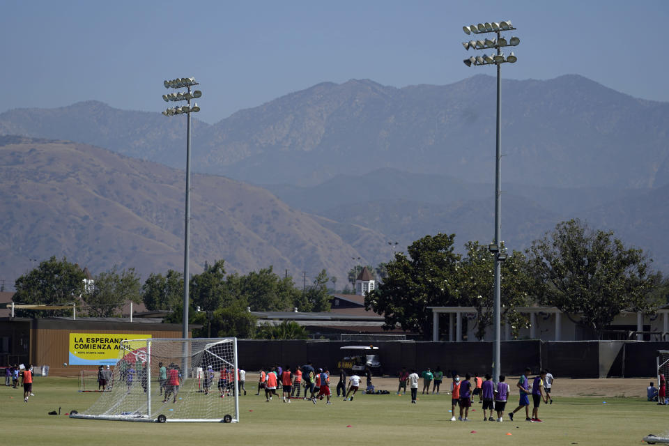 Children play soccer at an emergency shelter for migrant children Friday, July 2, 2021, in Pomona, Calif. The Biden administration on Friday gave a rare look inside an emergency shelter it opened to house migrant children crossing the U.S.-Mexico border alone, calling the California facility a model among its large-scale sites, some of which have been plagued by complaints. (AP Photo/Marcio Jose Sanchez, Pool)