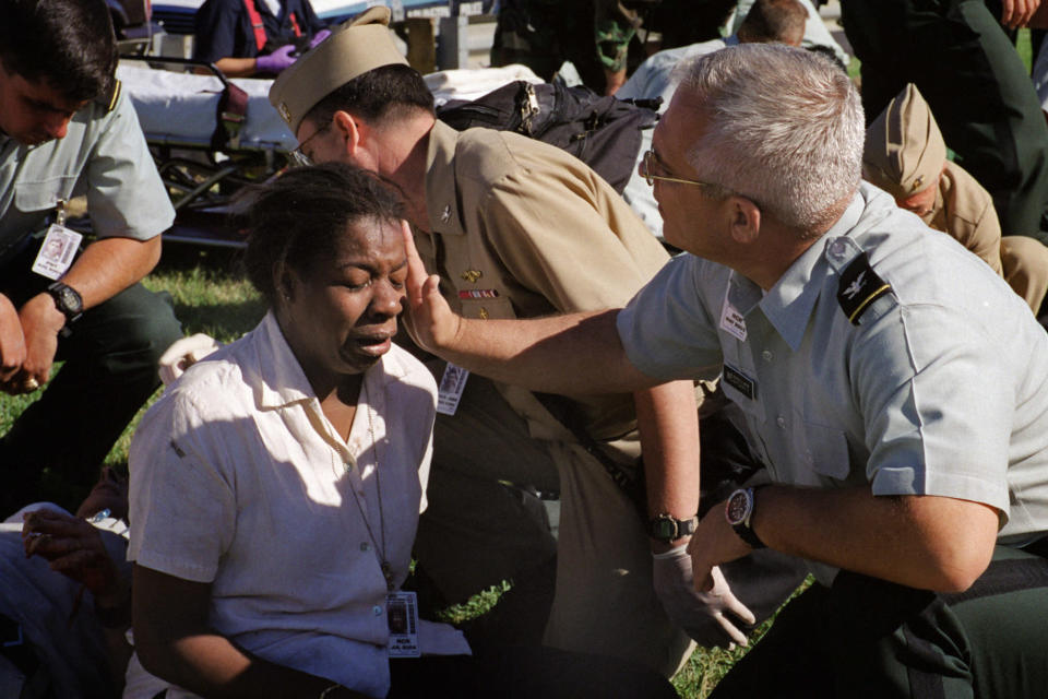 Deputy chief of the Army Reserve, Col. Malcolm Bruce Westcott, comforts Pentagon employee Racquel Kelley while giving her medical aid outside the Pentagon in Washington on Tuesday, Sept. 11, 2001. (AP Photo/Will Morris)