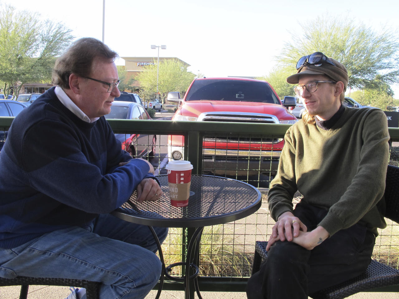 "<p> Christopher Farstad, right, a musician from Minneapolis, speaks with his father, James, at a coffee shop Friday, Dec. 9, 2016, in Gilbert, Ariz. Farstad was among a group of people attending a music event inside a warehouse in Oakland, Calif., on Friday night, Dec 2, 2016, when a fire tore through the building, killing dozens of people. He described the scene as a ""hellish situation."" (AP Photo/Brian Skoloff) </p>"