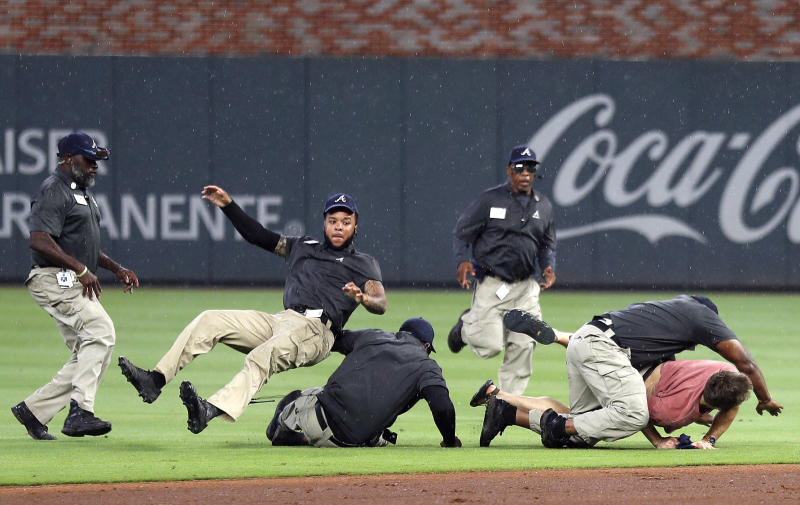 Members of Atlanta Braves security staff tackle a fan who ran onto the field during a rain delay in the sixth inning of a baseball game against the New York Mets, Monday, June 17, 2019, in Atlanta. (AP Photo/John Bazemore)