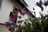 Marlene Beltran, 14, left, and her brother Felipe Beltran, 5, speak during an interview outside their home in Funza, Colombia, Wednesday, May 13, 2020. While schools are closed during the lockdown to curb the spread of COVID-19, teachers in the municipality of Funza broadcast their lessons through the radio station because many students do not have access to the Internet. (AP Photo/Fernando Vergara)