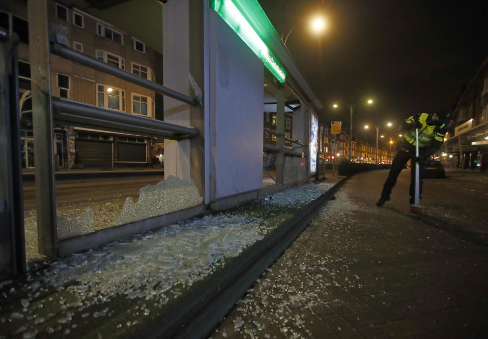 A police officer sweeps up glass from a bus stop that was smashed in protests against a nation-wide curfew in Rotterdam, Netherlands, Monday, Jan. 25, 2021. The Netherlands Saturday entered its toughest phase of anti-coronavirus restrictions to date, imposing a nationwide night-time curfew from 9 p.m. until 4:30 a.m. in a bid to control the COVID-19 infection rate. (AP Photo/Peter Dejong)
