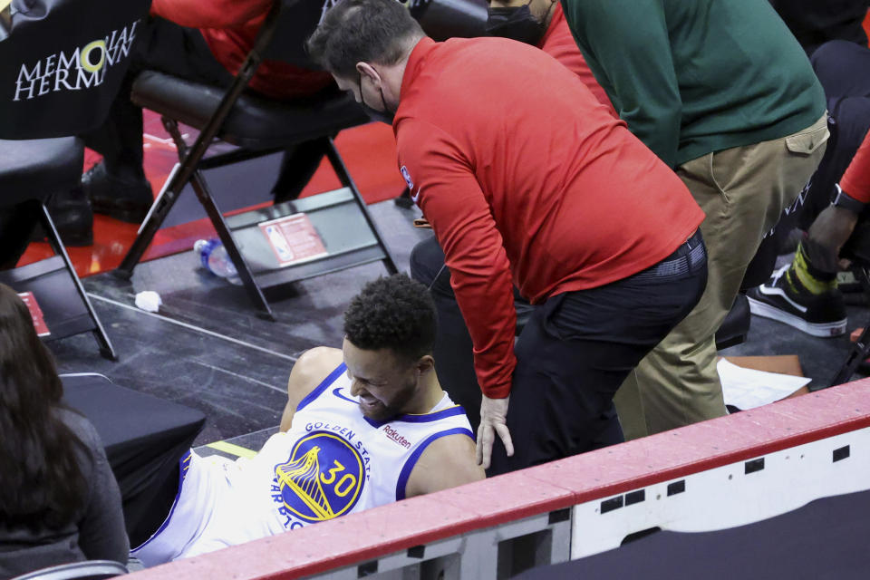Golden State Warriors' Stephen Curry after falling into the Houston bench